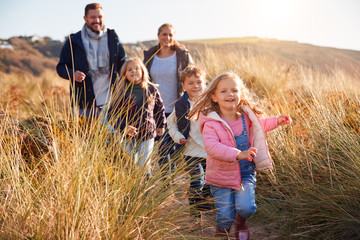 Family Walking Along Path Through Sand Dunes Together