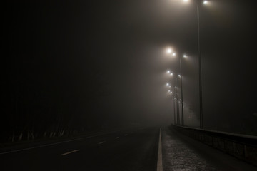 Empty road fog at night. Along the road lights are on. Fotomurales
