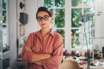Portrait of young female entrepreneur working in her studio, young professional manager wearing casual clothes working in Fotobehang