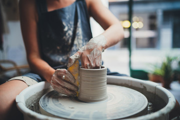 Cropped Image of Unrecognizable Female Ceramics Maker working with Pottery Wheel in Cozy Workshop Makes a Future Vase or Mug, Creative People Handcraft Pottery Class  - fototapety na wymiar