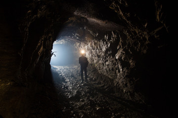 Underground gold mine shaft tunnel drift with miner and light