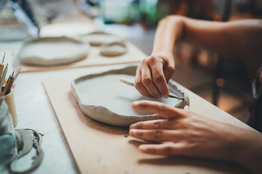 Closeup Image of Female Hands Works with Clay Makes Future Ceramic Plate, Professional Ceramic Artist Makes Classes of Hand Building in Modern Pottery Workshop, Creative People Handcrafted Design