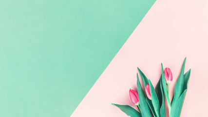 Bouquet of fresh pink tulips on pink and mint neo green background. Flat lay with copy space, Birthday gift. Valentines 8 March Women's or Mothers Day celebration greeting card or minimal banner Fototapete