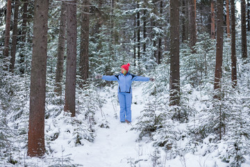 Adult woman walking in the winter forest. The concept of a healthy lifestyle for people aged.