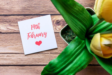 Valentine's day concept - 14th February and heart shape on paper note with yellow tulip flower