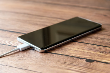 Smart phone power charging on top of wooden desk