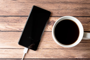Directly above shot of smart phone power charging on top of wooden desk with cup of coffee
