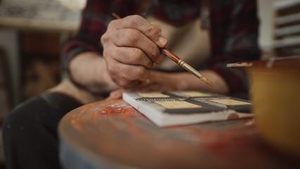 Craftsman decorates handmade terracotta