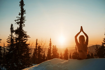 Garden Poster Lotus flower Young female wearing long hair dreads, seating in yoga lotus pose and meditating on sunrise in snow forest on mountain top. Cold frozen winter morning