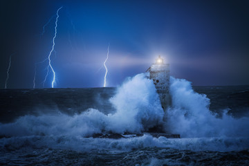 Lighthouse at night in the middle of a storm. Night stormy whether on the lighthouse hit by violent waves and lightning in background.