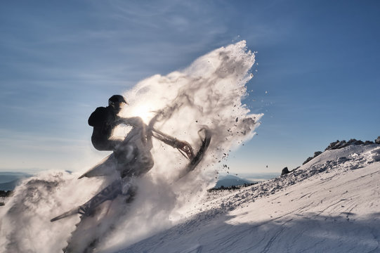 Snowbike rider in mountain valley. Modify dirt bike with snow splashes and trail. Snowmobile sport riding