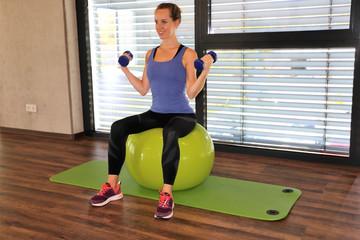 Junge Frau macht Übungen auf einem Gymnastikball