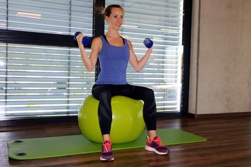 Young woman doing exercises on a gymnastics ball