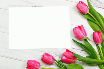 White paper for your text and bouquet of pink tulips on wooden background.