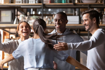 Happy diverse friends giving hug meeting girlfriend in cafe