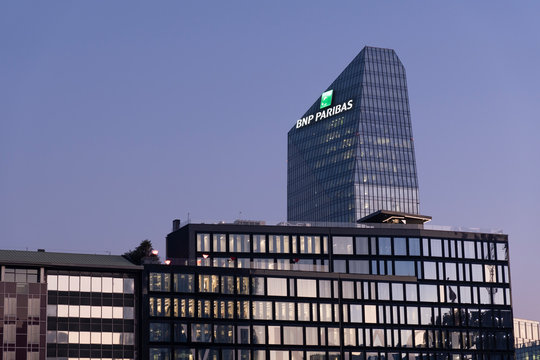Glass building headquarters of the French bank BNP Paribas with the logo sign illuminated at sunset. Milan, Italy - January 11, 2020.