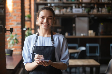 Portrait of smiling waitress in apron looking at camera
