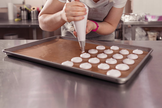 professional hands of chef making macarons of bakery bag. indoor shot