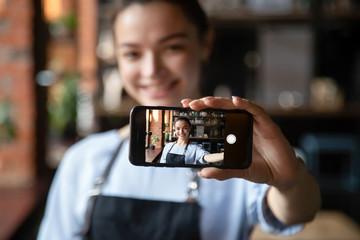 Smiling waitress hold cellphone making selfie in restaurant