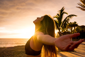 Healthy people lifestyle enjoying sunset and fitness activity alone - beautiful woman feel the sun and the ocean oxygen after workout sport session class - open arms and freedom breathe