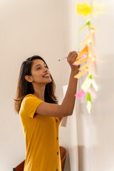 Smiling businesswoman working on adhesive notes in office