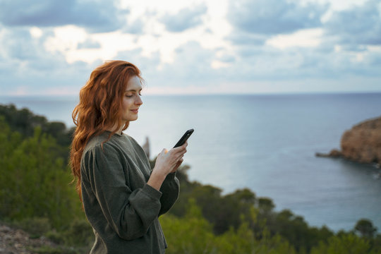Redheaded young woman using cell phone at the coast, Ibiza, Spain
