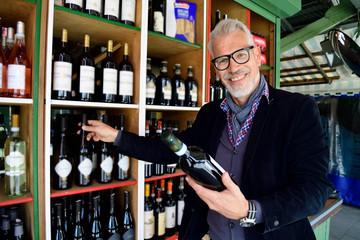 Portrait of smiling mature man choosing bottle of wine at a wine shop