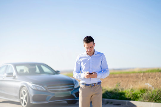 Young businessman with car on country road using smartphone