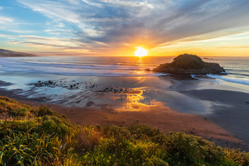 New Zealand, Tongaporutu, Clouds over sandy coastal beach at sunset with Motuotamatea island in background