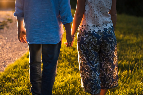 Couple hand in hand on a meadow at sunset