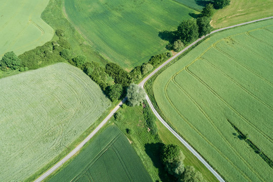 Germany, Bavaria, Aerial view of green countryside field and fork of empty road