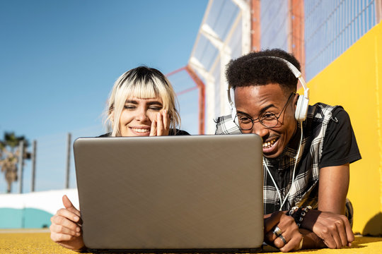 Portrait of young couple using headphones and laptop outdoors having fun