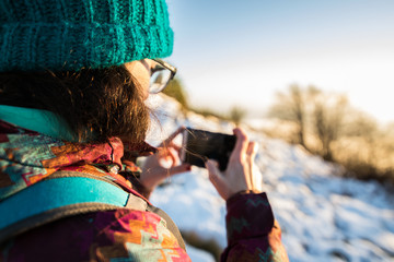girl taking pictures in the mountain with snow.