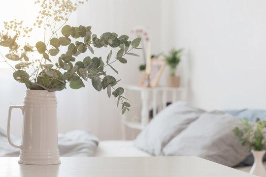 eucalyptus and gypsophila  in jug  in white bedroom