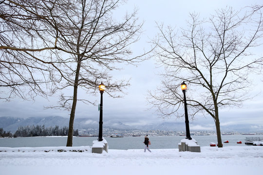 A woman walks along the seawall near Coal Harbour, with North Vancouver in the background, after a snow storm in downtown Vancouver