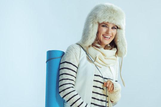 woman holding fitness mat against winter light blue background