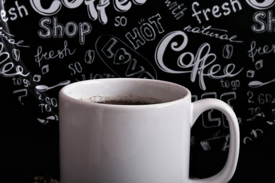 white coffee mug and black background with coffee beans