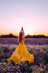 beautiful girl in a yellow dress posing in nature in lilac colors. gentle sunset sky