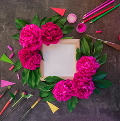 Artist Workspace with photo frame, white blank canvas, pink peony flowers with green leaves surrounded by variety of drawing supplies. Painting inspiration. Craft Art therapy. Creative working place.
