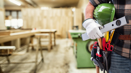 Close-up. Carpenter with hands protected by gloves holds helmet and level. Construction industry,...