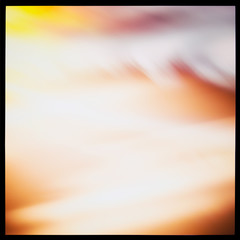 Abstract blurred light colored background, light spots on orange and yellow.