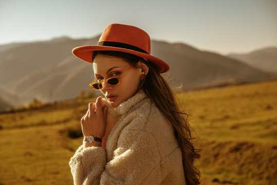 Outdoor close up fashion portrait of young beautiful confident brunette woman with freckled skin wearing stylish orange hat, sunglasses, wrist watch, faux fur coat, posing in mountain landscape