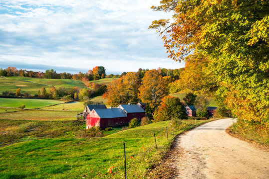Red barn along a gravel road in a rolling rural landscape in autumn. Beautiful fall foliage.