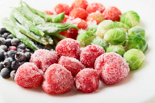 White plate with frozen food in a plate - strawberries with shadberry and brussels sprouts with asparagus beans