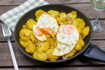 Hearty fried potatoes with fried egg. Arranged in the pan