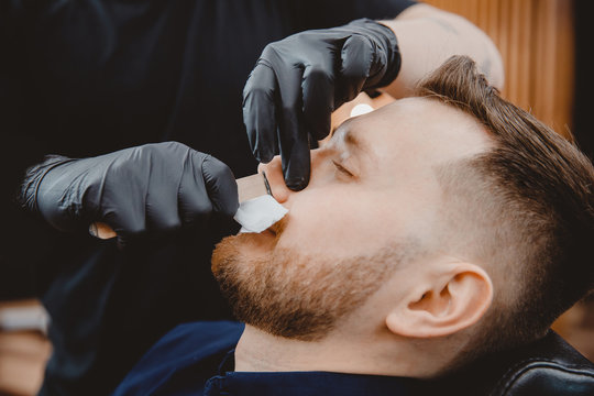 Hair removal with wax from man nose, beauty and care procedure depilation in barbershop