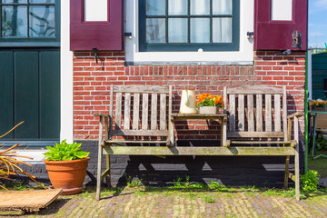 Traditional dutch house with wooden bench and flowers in the Zaanse Schans village, Netherlands. Famous tourism place.