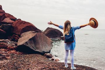 Woman traveler walking raised arms feeling happy on Red beach in Santorini island, Greece. Tourism, traveling