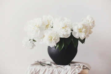 Stylish peony bouquet in black clay vase on linen fabric with scissors on rustic background. White peonies rural still life. Hello spring wallpaper. Happy Mothers day. Space text