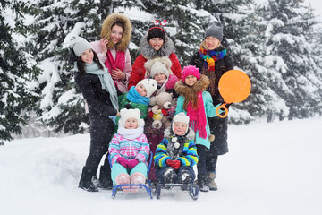 mothers with children with a sled and a Teddy bear on the background of snow and Christmas trees. Winter entertainment.